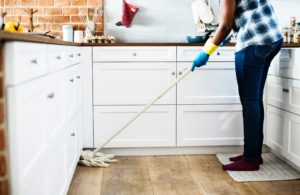 person mopping the floor of a kitchen