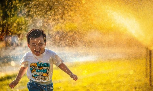 child running in sprinkler