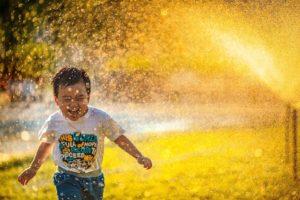 child running in sprinkler